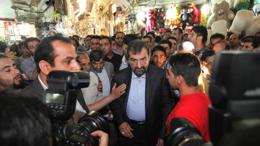 "FILE-In this file photo taken on Tuesday, May 28, 2013, Iranian presidential candidate Mohsen Rezaei, center, a former chief of the elite Revolutionary Guard, walks through the old main bazaar of Tehran, after his press conference. Iran's hard-liners are hoping they can benefit from the election of U.S. President Donald Trump, arguing that their own country needs a tougher leader to stand up to an American president whose administration has put the Islamic Republic ""on notice."" (AP Photo/Vahid Salemi, File)"