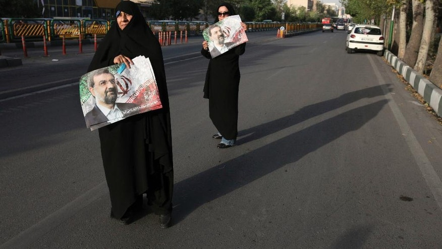 "FILE-In this file photo taken on Thursday, June 6, 2013, two female supporters of the Iranian presidential candidate, Mohsen Rezaei, a former commander in Iran's Revolutionary Guard, hold his posters, in a street campaign, in Tehran, Iran. Iran's hard-liners are hoping they can benefit from the election of U.S. President Donald Trump, arguing that their own country needs a tougher leader to stand up to an American president whose administration has put the Islamic Republic ""on notice.""(AP Photo/Vahid Salemi, File)"