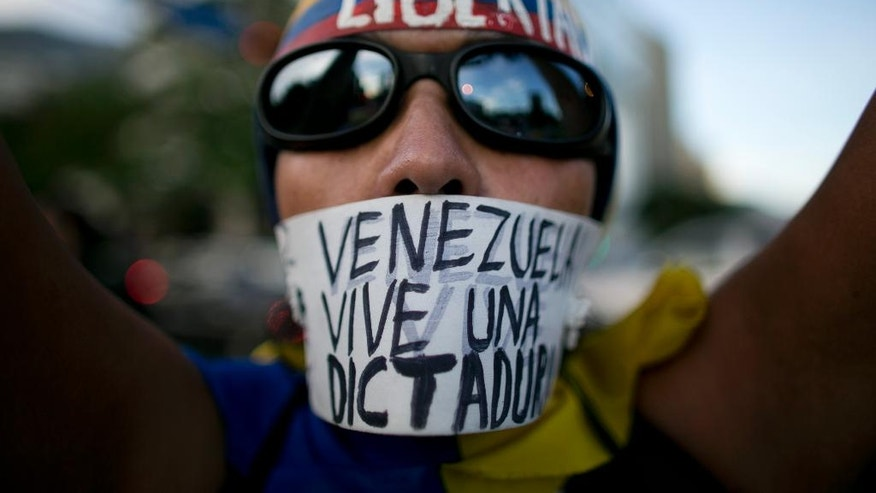"A woman wears a banner over her mouth with a message that reads in Spanish: ""Venezuela lives in a dictatorship"" during a protest, in Caracas, Venezuela, Friday, March 31, 2017. Venezuelans have been thrust into a new round of political turbulence after the government-stacked Supreme Court gutted congress of its last vestiges of power, drawing widespread condemnation from foreign governments and sparking protests in the capital. (AP Photo/Ariana Cubillos)"