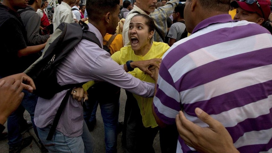 An opposition member, center, argues with a supporter of Venezuela's President Nicolas Maduro during a protest outside of Venezuela's General Prosecutor's office in Caracas, Venezuela, Friday, March 31, 2017. Venezuelans have been thrust into a new round of political turbulence after the government-stacked Supreme Court gutted congress of its last vestiges of power, drawing widespread condemnation from foreign governments and sparking protests in the capital. (AP Photo/Fernando Llano)