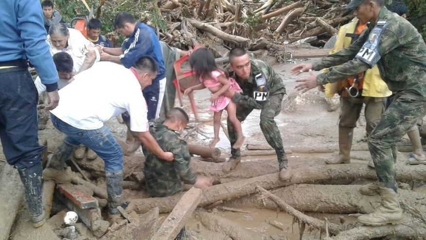 In this handout photo released by the Colombian National Army, soldiers rescue a child in Mocoa, Colombia, Saturday, April 1, 2017, after an avalanche of water from an overflowing river swept through the city as people slept. The incident triggered by intense rains left at least 100 people dead in Mocoa, located near Colombia's border with Ecuador. (Colombian Army Photo via AP)