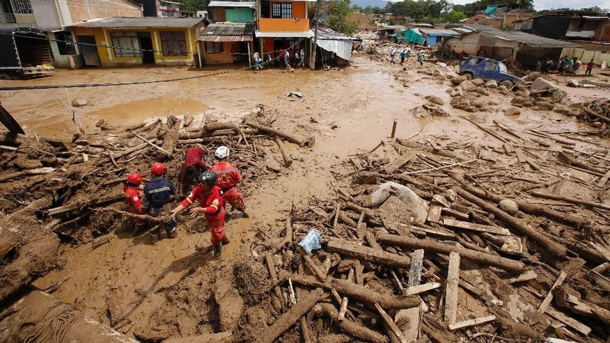 Rescuers search for survivors in Mocoa, Colombia, Sunday, April 2, 2017. A grim search for the missing resumed at dawn Sunday in southern Colombia after surging rivers sent an avalanche of floodwaters, mud and debris through a city, killing at least 200 people and leaving many more injured and homeless. (AP Photo/Fernando Vergara)