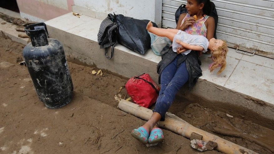A girl holds a doll rescued from her damaged house in Mocoa, Colombia, Sunday, April 2, 2017. A grim search for the missing resumed at dawn Sunday in southern Colombia after surging rivers sent an avalanche of floodwaters, mud and debris through a city, killing at least 200 people and leaving many more injured and homeless. (AP Photo/Fernando Vergara)