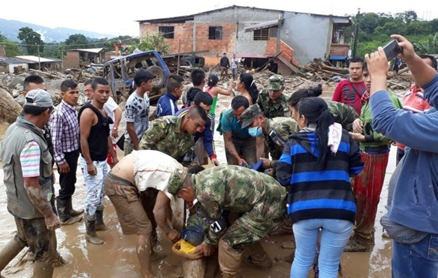 In this handout photo released by the Colombian National Army, soldiers carry a victim on a stretcher, in Mocoa, Colombia, Saturday, April 1, 2017, after an avalanche of water from an overflowing river swept through the city as people slept. The incident triggered by intense rains left at least 100 people dead in Mocoa, located near Colombia's border with Ecuador. (Colombian Army Photo via AP)