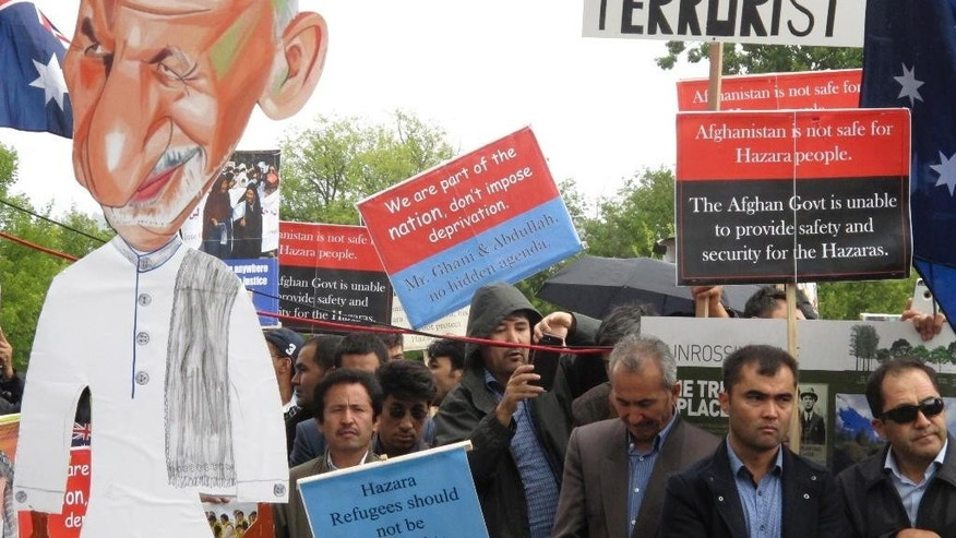 Protesters with a cutout of Afghan President Ashraf Ghani demonstrate against his visit to Australia outside Government House where Ghani met with Governor-General Peter Cosgrove, in Canberra Monday, April 3, 2017. Hundreds of protesters demonstrated against his visit, calling for his government to end discrimination against the Hazara ethnic minority and to refuse to repatriate asylum seekers rejected by Australia. (AP Photo/Rod McGuirk)