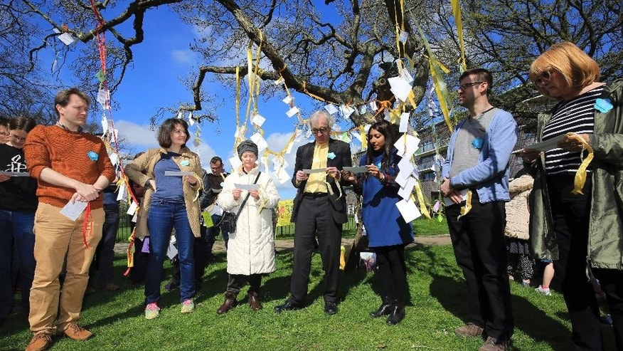 Richard Ratcliffe, left, husband of Nazanin Zaghari-Ratcliffe, listens to messages of support in Fortune Green, West Hampstead, Sunday April 2, 2017, to mark 365 days since this British-Iranian woman was imprisoned in Tehran. Zaghari-Ratcliffe was detained for allegedly trying to overthrow the cleric-run government. The dual national was returning home to Britain after visiting her family in Tehran with her toddler daughter. (Gareth Fuller/PA via AP)