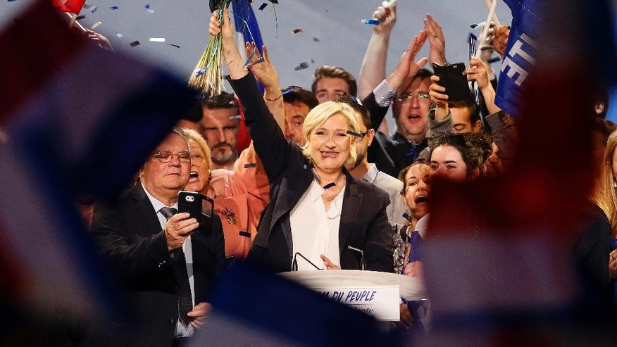 Far-right candidate for the presidential election Marine Le Pen holds flowers after she delivers a speech during a meeting in Bordeaux, southwestern France, Sunday, April 2, 2017. Polls suggest that Le Pen and independent centrist Emmanuel Macron are the two top contenders in the election. The top two vote-getters on April 23 will compete in a presidential runoff on May 7. (AP Photo/Bob Edme)