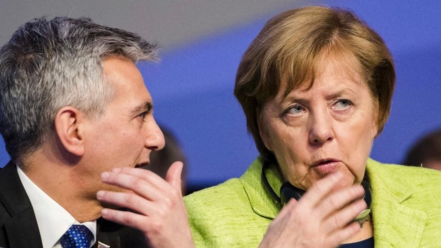 Maltese opposition Nationalist Party leader Simon Busuttil, left, talks with German Chancellor Angela Merkel at the European People's Party congress, in St. Julian's, Malta, Thursday, March 30, 2017. (AP Photo/Rene Rossignaud)