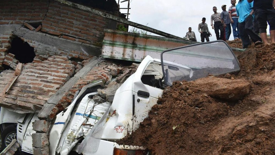 Rescuers inspect the damage in a neighborhood hit by a landslide in the village of Banaran, Ponorogo, East Java, Indonesia, Saturday, April 1, 2017. More than two dozen people were reported missing on Saturday after the rain-triggered landslide struck a village on Indonesia's main island of Java. (AP Photo/Firdaus)