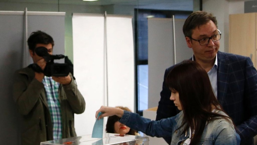 Current Serbian Prime Minister and presidential candidate Aleksandar Vucic, right, casts his ballot with his daughter Milica at a polling station, in Belgrade, Serbia, Sunday, April 2, 2017. Around 6.7 million voters in Serbia choose a new president in an election Sunday that will test the popularity of the dominant, populist prime minister, Aleksandar Vucic, against 10 beleaguered candidates from the fragmented opposition. (AP Photo/Darko Vojinovic)