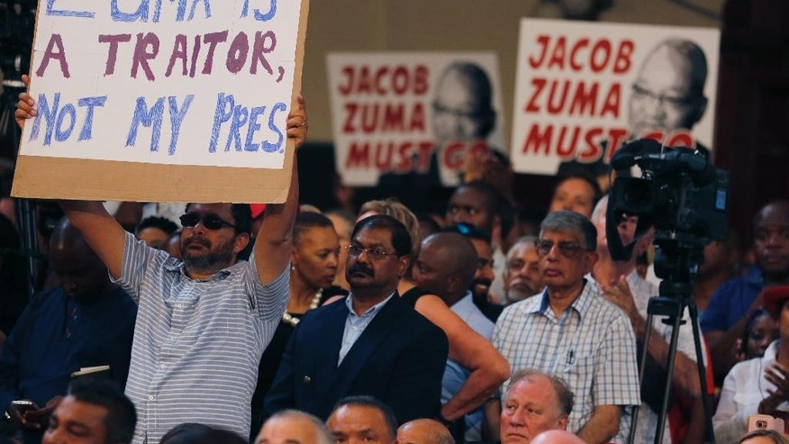 Protesters raise placards against South African President Jacob Zuma in Johannesburg, Saturday, April 1, 2017, during a memorial service for anti-apartheid stalwart Ahmed Kathrada, who died Tuesday. The memorial service for Kathrada turned into a protest against South African President Zuma. (AP Photo/Denis Farrell)