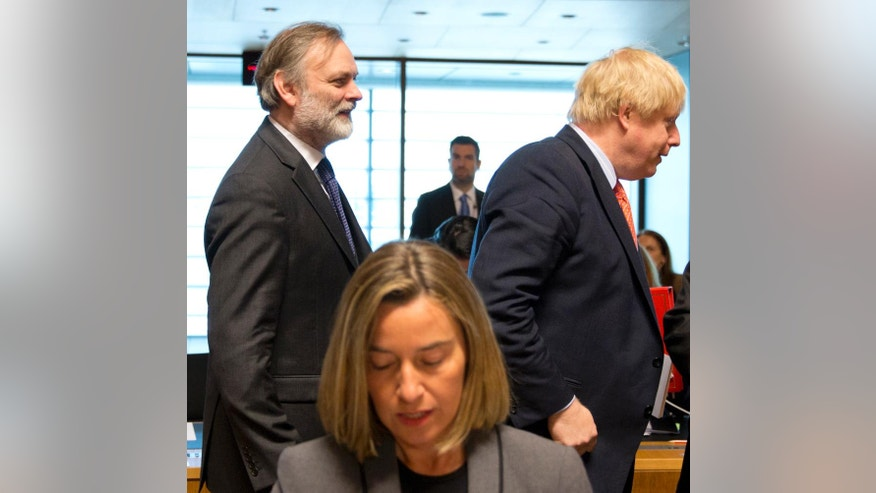 British Foreign Secretary Boris Johnson, right, and UK permanent representative to the EU Tim Barrow, left, walk by European Union High Representative Federica Mogherini during a meeting of EU foreign ministers at the EU Council building in Luxembourg on Monday, April, 2017. European Union foreign ministers meet Monday to discuss the situation in Syria and Libya. (AP Photo/Virginia Mayo)