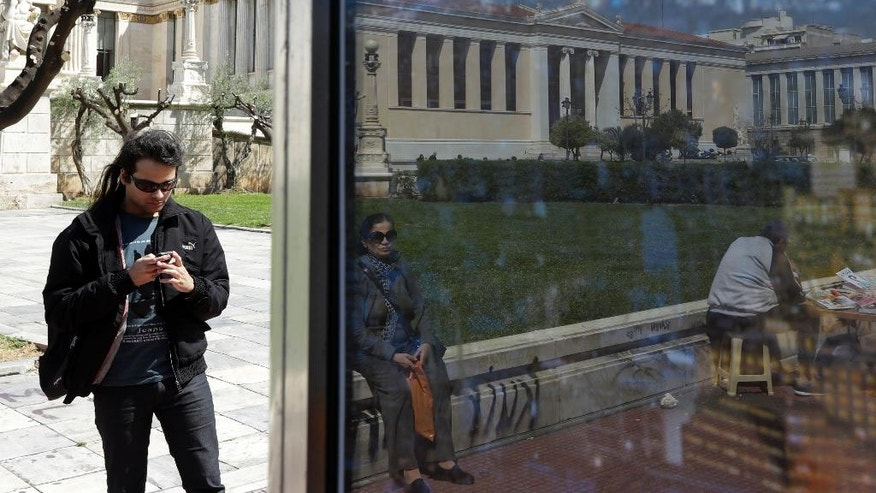 A man checks his cellphone as a woman is reflected on a bus stop window pane next to the Academy of Athens, on Friday, March 31, 2017. Greece and its international creditors are stepping up talks on issues holding up the release of more loans to keep the country's debt-wracked economy afloat. (AP Photo/Thanassis Stavrakis)