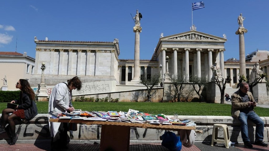 A woman checks a book at a street vendor's stall next to the Academy of Athens, on Friday, March 31, 2017. Greece and its international creditors are stepping up talks on issues holding up the release of more loans to keep the country's debt-wracked economy afloat. (AP Photo/Thanassis Stavrakis)