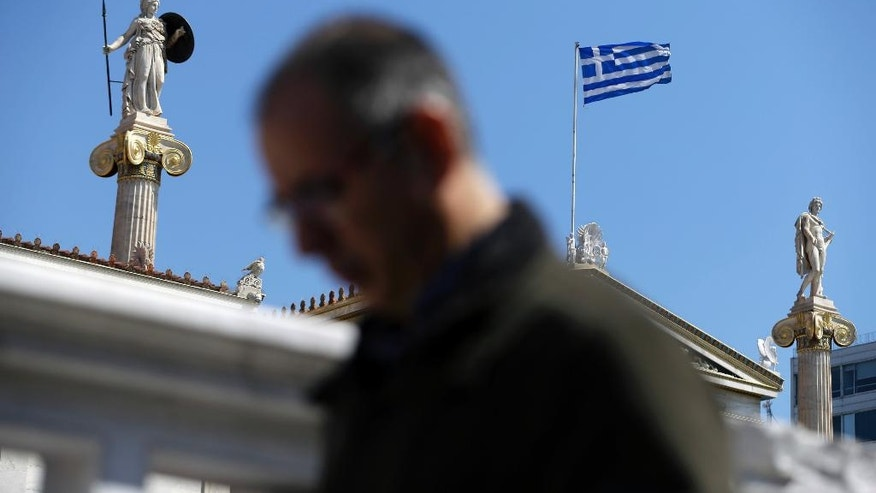 A commuter enters a metro station next to the Academy of Athens, on Friday, March 31, 2017. Greece and its international creditors are stepping up talks on issues holding up the release of more loans to keep the country's debt-wracked economy afloat. (AP Photo/Thanassis Stavrakis)