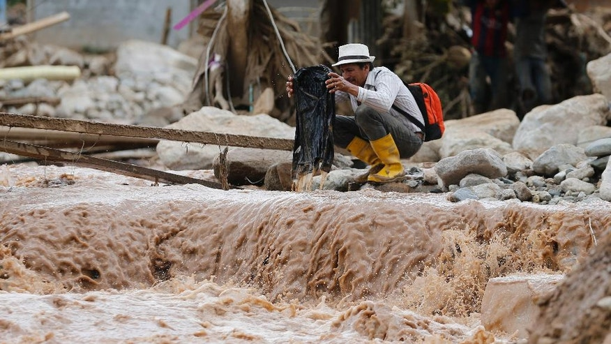 A man washes a shirt in muddy water in Mocoa, Colombia, Sunday, April 2, 2017. A grim search for the missing resumed at dawn Sunday in southern Colombia after surging rivers sent an avalanche of floodwaters, mud and debris through a city, killing at least 200 people and leaving many more injured and homeless. (AP Photo/Fernando Vergara)