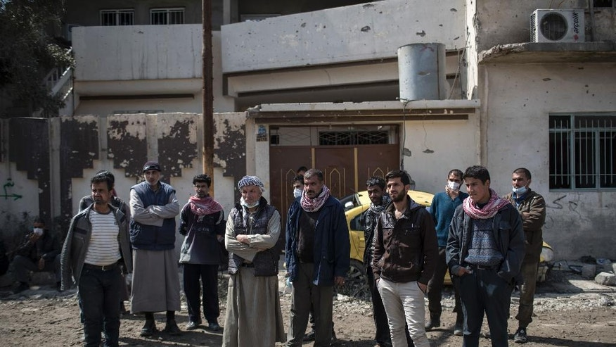 In this March 24, 2017 photo, Mahmoud Salem Ismail, second from right, other relatives and neighbors watch as civil protection rescue workers remove bodies of civilians killed in an airstrike in west Mosul, Iraq. Ismail first found the body of his nephew. Then as rescue workers pulled more and more bodies out of the pile of concrete that was once his sister's home in western Mosul, it was too much for Mahmoud Salem Ismail. He collapsed next to the body bags on the ground. (AP Photo/Felipe Dana)