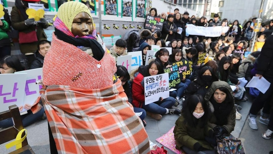 "FILE - In this Jan. 11, 2017, file photo, students gather near a ""comfort-woman"" statue during a rally in front of the Japanese Embassy in Seoul, South Korea. Japan said Monday, April 3 that it is returning its recalled ambassador to South Korea despite a continuing impasse over the ""comfort woman"" statue, but insisted it is not caving in to Seoul's position. Foreign Minister Fumio Kishida announced that Ambassador Yasumasa Nagamine will fly back to Seoul on Tuesday, along with the Japanese consul-general in the South Korean city of Busan. (AP Photo/Lee Jin-man, File)"