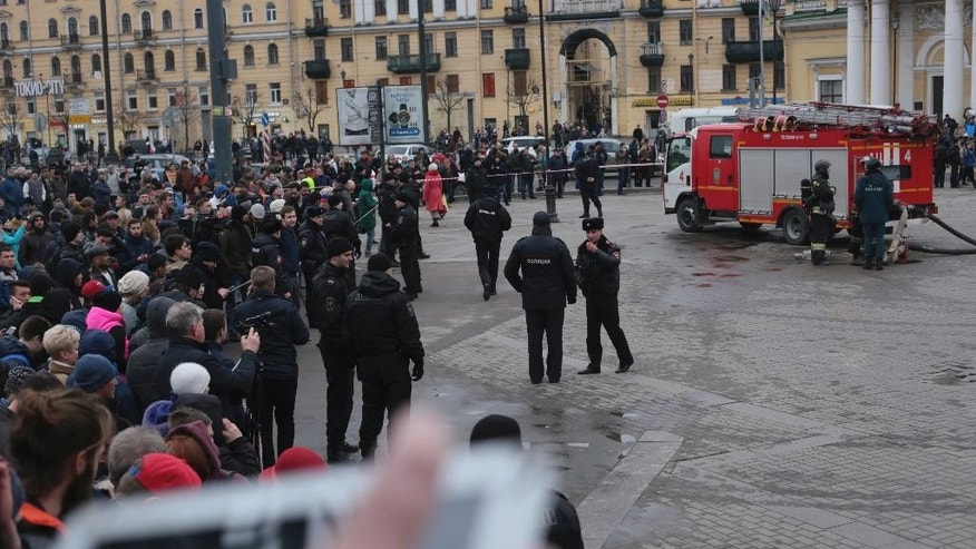 Russian police and emergency service officers block an area next to fire trucks at Sadovaya Square after explosion in St.Petersburg subway in St. Petersburg, Russia, Monday, April 3, 2017. The subway in the Russian city of St. Petersburg an explosion on a subway train. (AP Photo/Yevgeny Kurskov)
