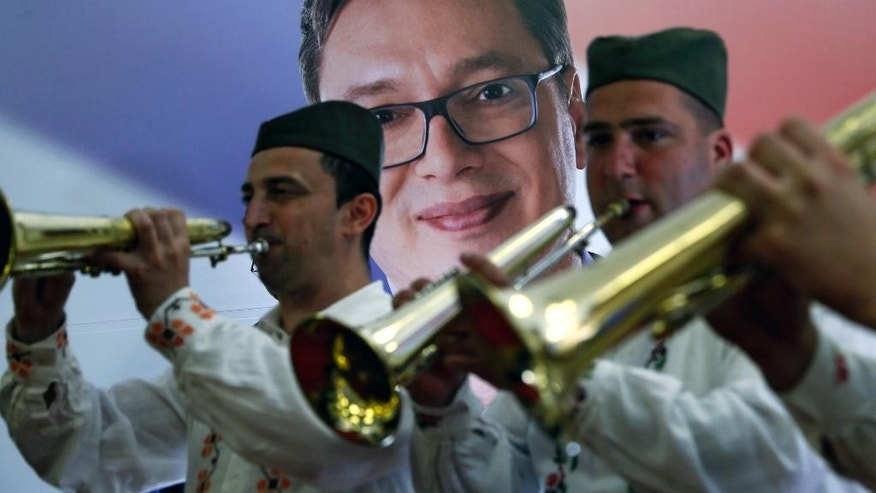 A trumpet band wearing traditional Serbian hats play in front of a picture of current Serbian Prime Minister and presidential candidate Aleksandar Vucic at a press conference after claiming victory in the presidential election, in Belgrade, Serbia, Sunday, April 2, 2017. Vucic claimed victory Sunday in the presidential election that was a test of his authoritarian rule amid growing Russian influence in the Balkan region. (AP Photo/Darko Vojinovic)