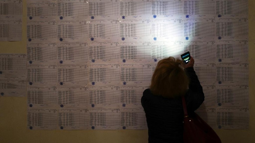 A woman uses the light of her cell phone to search for her name to vote, at a polling station during a parliamentary election in Yerevan, Armenia, Sunday, April 2, 2017. Armenians voted Sunday in the country's first parliamentary election since the ex-Soviet nation modified its constitution to expand the powers of parliament and the prime minister. (PAN Photo, Vahan Stepanyan/Photo via AP)