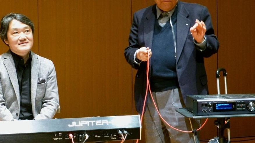 In this Jan. 11, 2013 photo, Ikutaro Kakehashi, right, speaks next to composer Akira Senju during a press conference after he received a Grammy, for developing MIDI, or Musical Instrumental Digital Interface, technology, which digitally connects instruments, in Hamamatsu, central Japan.  Kakehashi,  who pioneered digital music and founded synthesizer giant Roland Corp., has died, his company ATV Corp. said Monday, April 3, 2017.  He was 87.  (Kyodo News via AP)