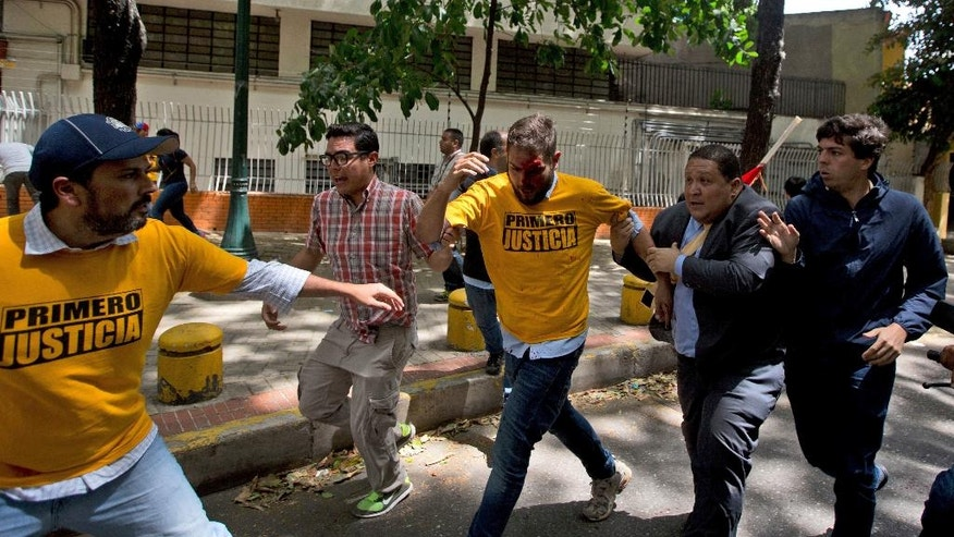 Opposition lawmaker Juan Requesens, center, is evacuated by his colleagues after begin injured by alleged pro government supporters as they protest outside of the Ombudsman's offices in Caracas, Venezuela, Monday, April 3, 2017. A group of opposition lawmakers was attacked by suspected followers of the government during a demonstration in the center of the capital that left at least one injured congressman. (AP Photo/Fernando Llano)