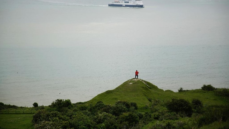 FILE - In this June 9, 2016 file photo a Chinese tourist looks out from a section of the White Cliffs of Dover in south east England towards the Strait of Dover, marking the narrowest point of the English Channel which separates Britain from mainland Europe. A period of slow erosion, then a cataclysmic split. Britain's geographic separation from the European mainland foreshadowed the present Brexit process in many ways, a new study shows. (AP Photo/Matt Dunham, file)