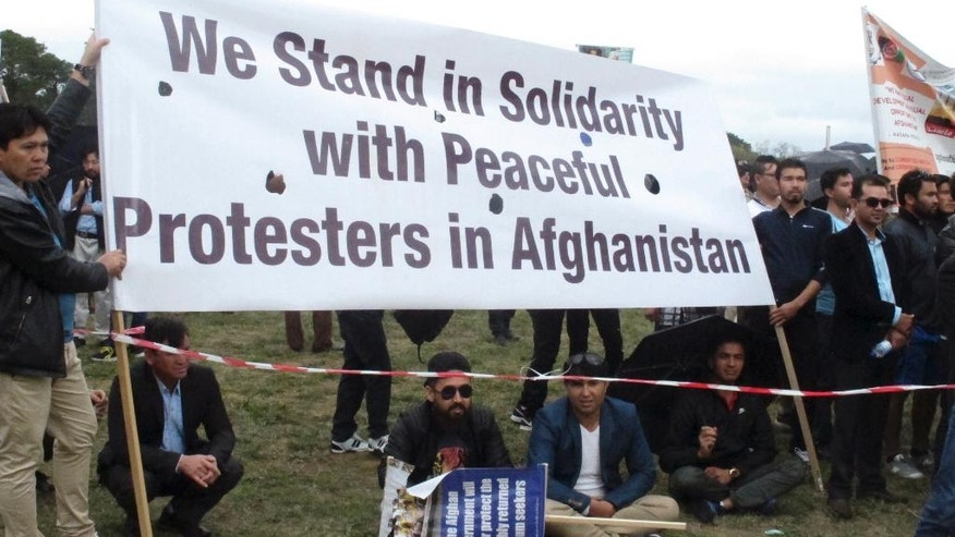 Protesters demonstrate against Afghan President Ashraf Ghani's visit to Australia, outside Government House where Ghani met with Governor-General Peter Cosgrove, in Canberra Monday, April 3, 2017. Hundreds of protesters demonstrated against his visit, calling for his government to end discrimination against the Hazara ethnic minority and to refuse to repatriate asylum seekers rejected by Australia. (AP Photo/Rod McGuirk)
