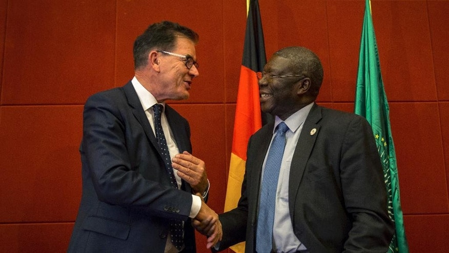 "Germany's Federal Minister for Economic Cooperation and Development Gerd Mueller, left, shakes hands with Deputy Chairperson of the African Union Commission Kwesi Quartey, right, after making an address at a hotel in Addis Ababa, Ethiopia Tuesday, April 4, 2017. While announcing Tuesday what he called a ""Marshall Plan with Africa"" focused on improving economic growth, security and rule of law, Mueller said the United States' plan to spend more on its military won't guarantee peace and criticised the Trump administration's proposed cuts to foreign aid. (AP Photo/Mulugeta Ayene)"