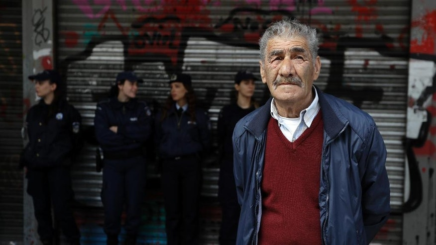 An elderly man stands in front of police officers, during a protest outside the Labor Ministry in Athens, Tuesday, April 4, 2017. About 3,000 pensioners marched through the Greek capital to protest years of cuts to their pensions under the country's bailout commitments. (AP Photo/Thanassis Stavrakis)