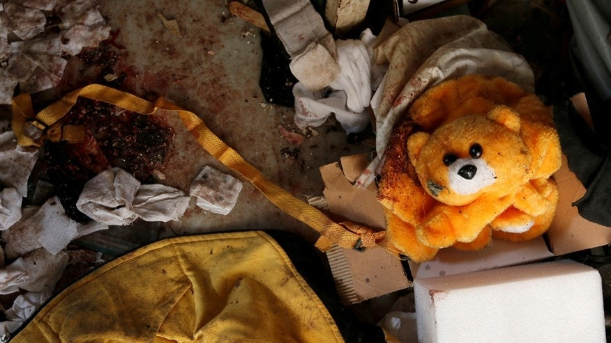 A teddy bear bag lies on the ground near blood stains in a damaged room inside National Hospital after explosions hit the Syrian city of Jableh, May 23, 2016. REUTERS/Omar Sanadiki - RTSFL1J