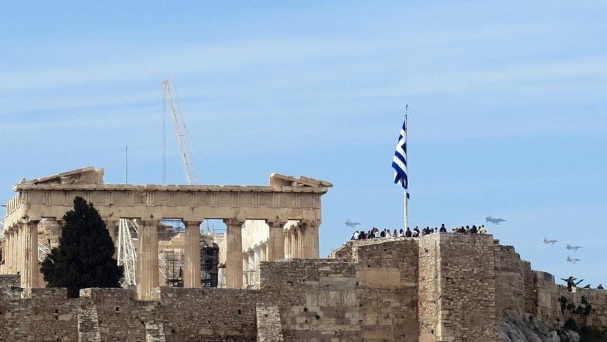 "Tourists on the Acropolis hill watch fighter jets flying in formation over Athens on Tuesday, April 4, 2014, as part of the international exercise ""Iniohos 2017."" (AP Photo/Theodora Tongas)"