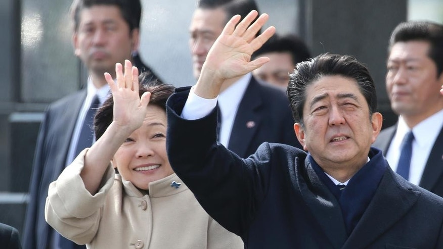 FILE - In this Feb. 28, 2017 file photo, Japan's Prime Minister Shinzo Abe and his wife Akie wave as Emperor Akihito and Empress Michiko depart for Vietnam from the Haneda International Airport in Tokyo. Opposition politicians on Tuesday, April 4, criticized a decision by Japan's Cabinet to allow schools to study a 19th century imperial order on education that was banned after World War II for promoting militarism and emperor worship, saying it's a sign that Abe's government is becoming more nationalistic. The Cabinet adopted the policy Friday, March 31. (AP Photo/Shizuo Kambayashi, File)