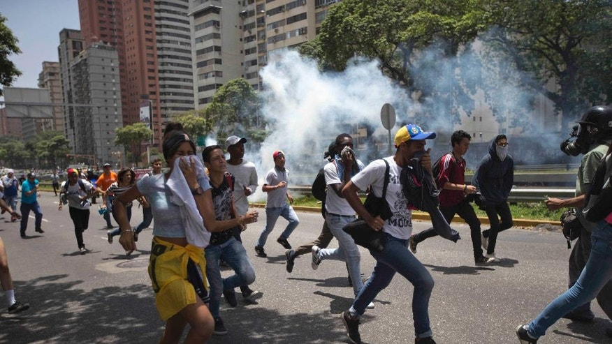 People run away from tear gas during clashes between opposition members and police forces in Caracas, Venezuela, Tuesday, April 4, 2017. The demonstrators were trying to accompany opposition lawmakers in a march to the National Assembly for a session where they planned to debate removing Supreme Court magistrates who issued a ruling last week removing the last vestiges of power from the opposition-controlled congress. (AP Photo/Ariana Cubillos)