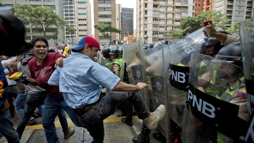 Demonstrators fights with Venezuelan National Police officers during clashes between opposition members and police forces in Caracas, Venezuela, Tuesday, April 4, 2017. Venezuelan riot police have launched pepper spray and tear gas to disperse an angry crowd of several thousand anti-government demonstrators trying to make their way to congress in Caracas. (AP Photo/Fernando Llano)