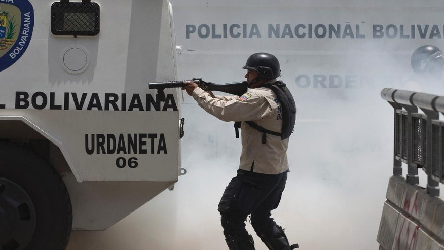 A Bolivarian National Police officer fires rubber bullets towards demonstrators during clashes with opposition members in Caracas, Venezuela, Tuesday, April 4, 2017. The demonstrators were trying to accompany opposition lawmakers in a march to the National Assembly for a session where they planned to debate removing Supreme Court magistrates who issued a ruling last week removing the last vestiges of power from the opposition-controlled congress. (AP Photo/Ariana Cubillos)