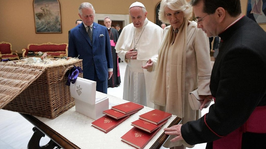 Pope Francis exchanges gifts with Britain's Prince Charles and his wife Camilla, Duchess of Cornwall, during a private audience at the Vatican, Tuesday, April 4, 2017. The heir to the British throne is on a three-country trip seen as an effort to reassure European Union nations that Britain remains a close ally despite its impending departure from the bloc. (L'Osservatore Romano/Pool Photo via AP)