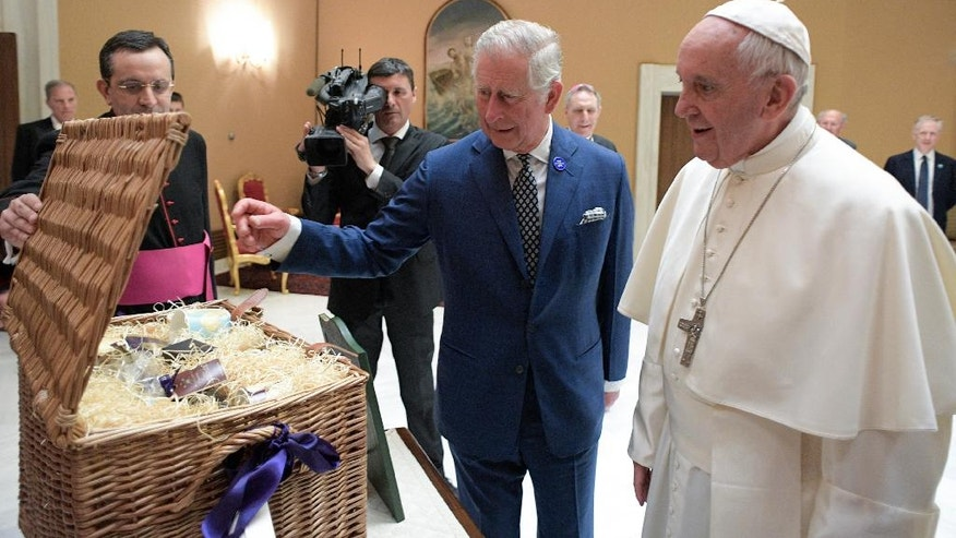 Pope Francis exchanges gifts with Britain's Prince Charles, during a private audience at the Vatican, Tuesday, April 4, 2017. The heir to the British throne is on a three-country trip seen as an effort to reassure European Union nations that Britain remains a close ally despite its impending departure from the bloc. (L'Osservatore Romano/Pool Photo via AP)