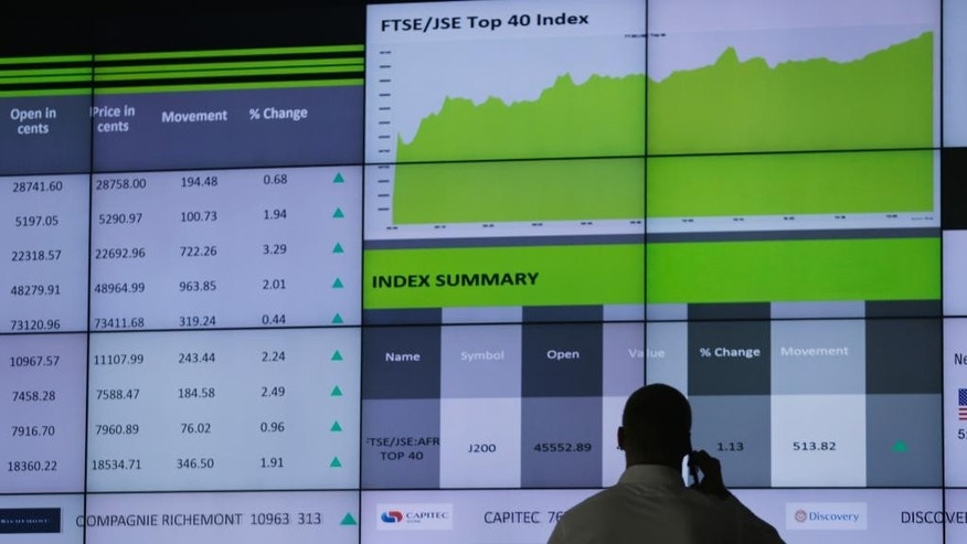 A worker at the  Stock Exchange in Johannesburg, South Africa uses his mobile phone Tuesday, April 4, 2017. South Africa's rand tumbled Monday after Standard & Poor's, a credit ratings agency, lowered the country to below investment grade, citing political instability and threats to economic growth. (AP Photo/Denis Farrell)