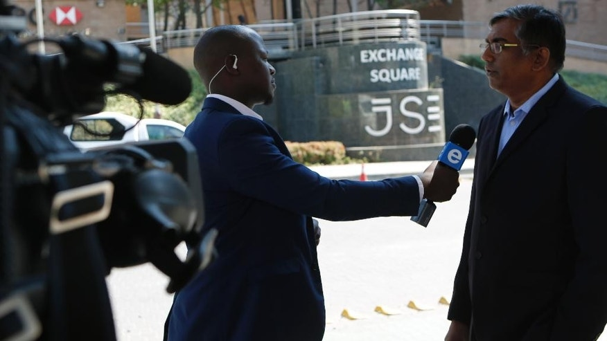 A local television station broadcasts live outside the Stock Exchange  in Johannesburg South Africa Tuesday, April 4, 2017. South Africa's rand tumbled Monday after Standard & Poor's, a credit ratings agency, lowered the country to below investment grade, citing political instability and threats to economic growth. (AP Photo/Denis Farrell)