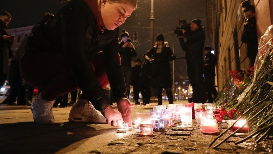 A woman lights a candle at a place near the Tekhnologichesky Institut subway station in St.Petersburg, Russia, Monday, April 3, 2017. A bomb blast tore through a subway train deep under Russia's second-largest city Monday, killing several people and wounding many more in a chaotic scene that left victims sprawled on a smoky platform. (AP Photo/Dmitri Lovetsky)