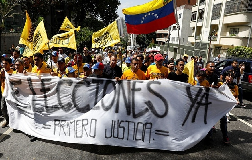 "Demonstrators carry a banner reading ""Elections now, justice first"" during an opposition rally in Caracas, Venezuela April 4, 2017. REUTERS/Carlos Garcia Rawlins - RTX34248"
