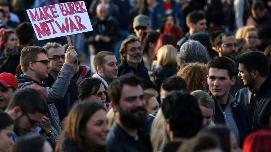 "A protester holds a banner reads: ""Make Burek not War ""(Burek is a dish popular over Eastern Europe), during a protest in Belgrade, Serbia, Tuesday, April 4, 2017. Several hundred mostly young people have gathered in Belgrade and other Serbian cities to protest against powerful leader Aleksandar Vucic's presidential election victory. (AP Photo/Darko Vojinovic)"