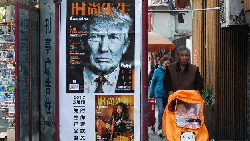 In this March 15, 2017 file photo, a man pushes a stroller past a magazine advertisement featuring U.S. President Donald Trump at a news stand in Shanghai, China. Asia's developing economies will see steady growth this year and the next, though the evolving policies of President Donald Trump's administration are a major uncertainty, according to the Asian Development Bank's latest report released Thursday, April 6, 2017. (Chinatopix via AP, File)