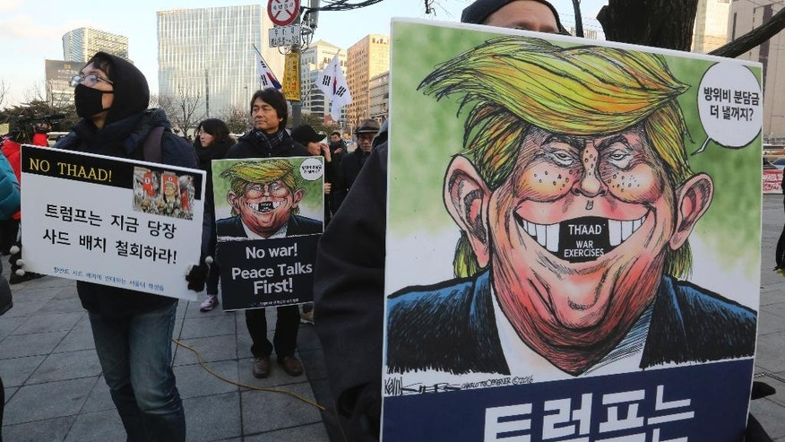 "In this Feb. 2, 2017 file photo, South Korean protesters hold signs with the words "" We oppose to deploy an advanced U.S. missile defense system called Terminal High-Altitude Area Defense, or THAAD "" and cartoons depicting U.S. President Donald Trump during a rally against U.S. Defense Secretary Jim Mattis' visit, in front of the government complex in Seoul, South Korea. Asia's developing economies will see steady growth this year and the next, though the evolving policies of President Donald Trump's administration are a major uncertainty, according to the Asian Development Bank's latest report released Thursday, April 6, 2017. (AP Photo/Ahn Young-joon, File)"