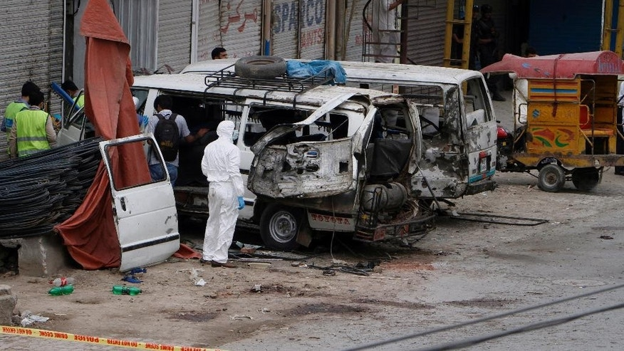 Pakistani investigators examine damage vehicles at the site of suicide bombing in Lahore, Pakistan, Wednesday, April 5, 2017. A suicide bomber detonated his explosives near a vehicle carrying census workers in eastern Pakistan on Wednesday, killing six people, two data collectors and four soldiers who were escorting them, a government spokesman and police said. (AP Photo/K.M. Chaudary)