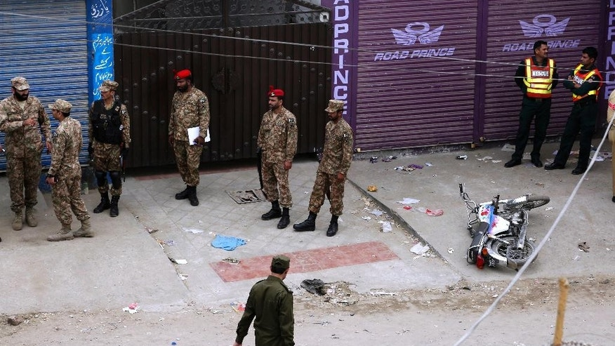 Pakistani army soldiers gather at the site of suicide bombing in Lahore, Pakistan, Wednesday, April 5, 2017. A suicide bomber detonated his explosives near a vehicle carrying census workers in eastern Pakistan on Wednesday, killing six people, two data collectors and four soldiers who were escorting them, a government spokesman and police said. (AP Photo/K.M. Chaudary)