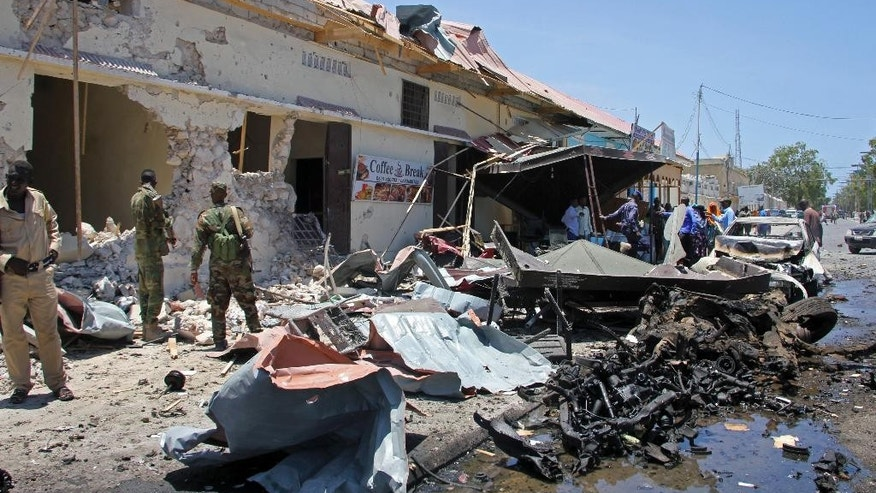 Somali security forces attend the scene of a car bomb attack on a restaurant in Mogadishu, Somalia Wednesday, April 5, 2017. The massive car bomb blast at a restaurant in Somalia's capital killed a number of people Wednesday, police said, with others injured in the attack near the ministries of internal security and youth and sports. (AP Photo/Farah Abdi Warsameh)