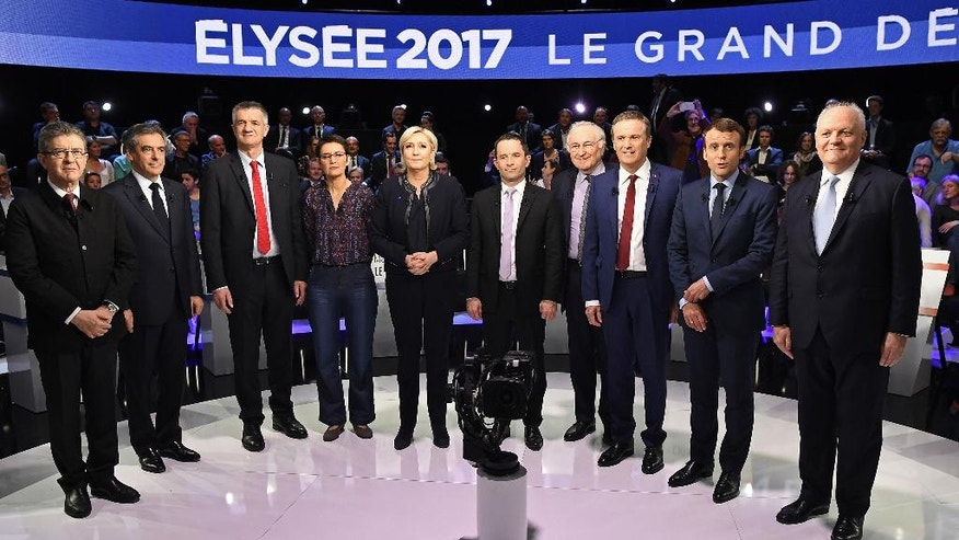From left to right, France's presidential candidates Jean-Luc Melenchon, Francois Fillon, Jean Lassalle, Nathalie Arthaud, Marine Le Pen, Benoit Hamon, Jacques Cheminade, Nicolas Dupont-Aignan, Emmanuel Macron and Francois Asselineau pose for a group photo prior to a television debate at French private TV channels BFM TV and CNews, in La Plaine-Saint-Denis, outside Paris, France, Tuesday, April 4, 2017. The 10 candidates in France's presidential race are preparing to face off in a crucial debate Tuesday evening, less than three weeks before the first round of the election. (Lionel Bonaventure/Pool Photo via AP)